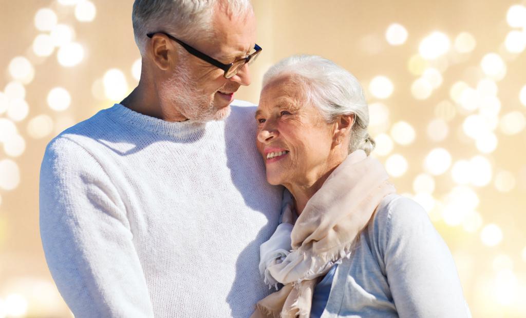 happy senior couple over festive lights background